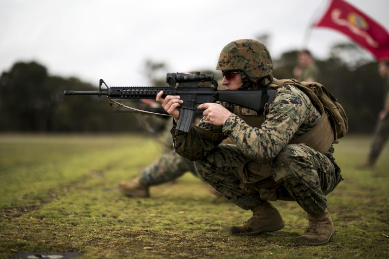 marine in the squatting position with M16A4 and Trijicon ACOG