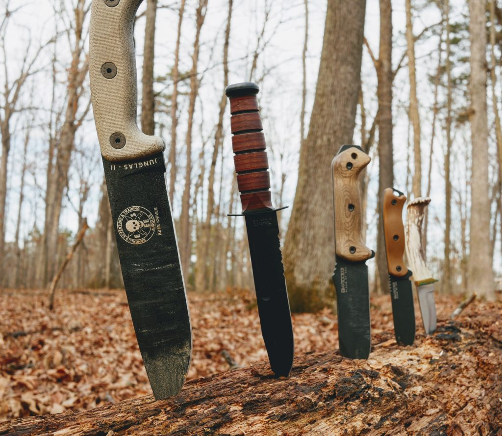 several examples of a field knife stuck into a log